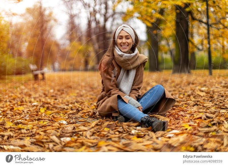 Portrait of smiling young woman in a park in autumn nature leaves freedom healthy trees yellow forest season public park relax serene tranquil fall outdoors