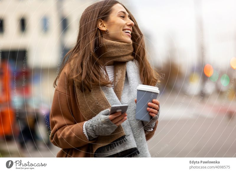 Smiling young woman with smart phone and coffee cup outdoors at urban setting autumn fall girl female beautiful weather coat fashion pretty attractive adult