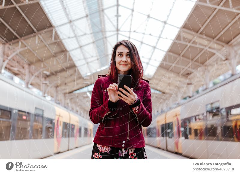 beautiful caucasian woman in train station ready to travel using mobile phone. Travel and lifestyle concept technology smart phone internet device connections