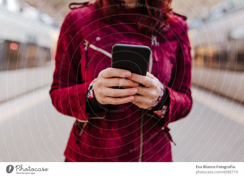 close up of beautiful caucasian woman in train station ready to travel using mobile phone. Travel and lifestyle concept technology smart phone internet device