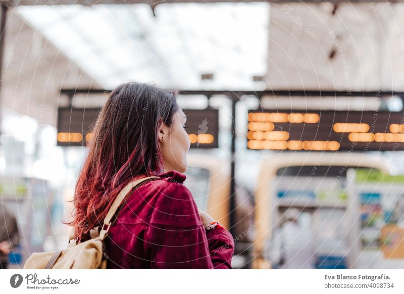 back view of backpacker woman in train station waiting to travel. Travel and lifestyle concept city public transport boards caucasian young trip screen