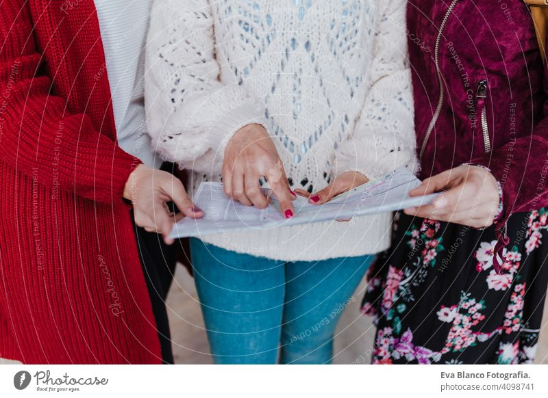 close up of group of three young caucasian women at train station reading a map. Travel and friendship concept unrecognizable travel together fun 3 board