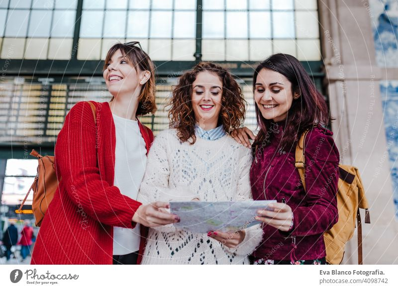 group of three young caucasian women at train station reading a map. Travel and friendship concept travel together fun 3 board backpacker city public transport