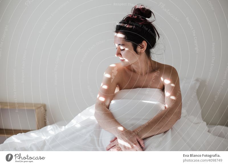 attractive young caucasian woman relaxing well in bed during morning time. Lady enjoys fresh soft bedding linen and mattress in bedroom white sheets lifestyle