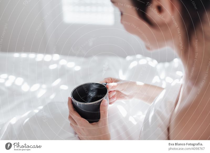attractive young caucasian woman relaxing well in bed during morning time. Lady enjoys cup of coffee in bedroom breakfast drink beverage hot tea drinking