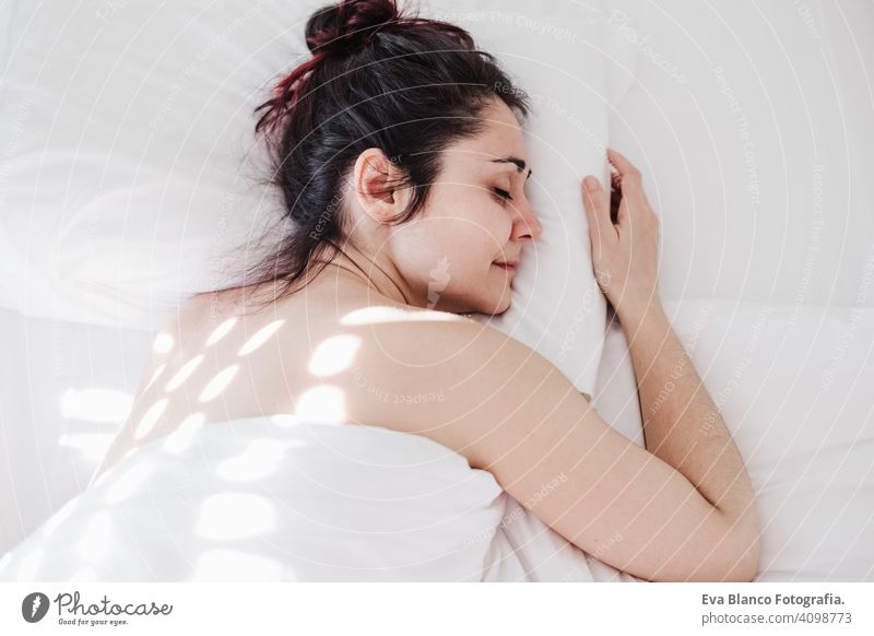 Top view of attractive young woman sleeping well in bed hugging soft white pillow. girl resting, good night sleep concept. Lady enjoys fresh soft bedding linen and mattress in bedroom