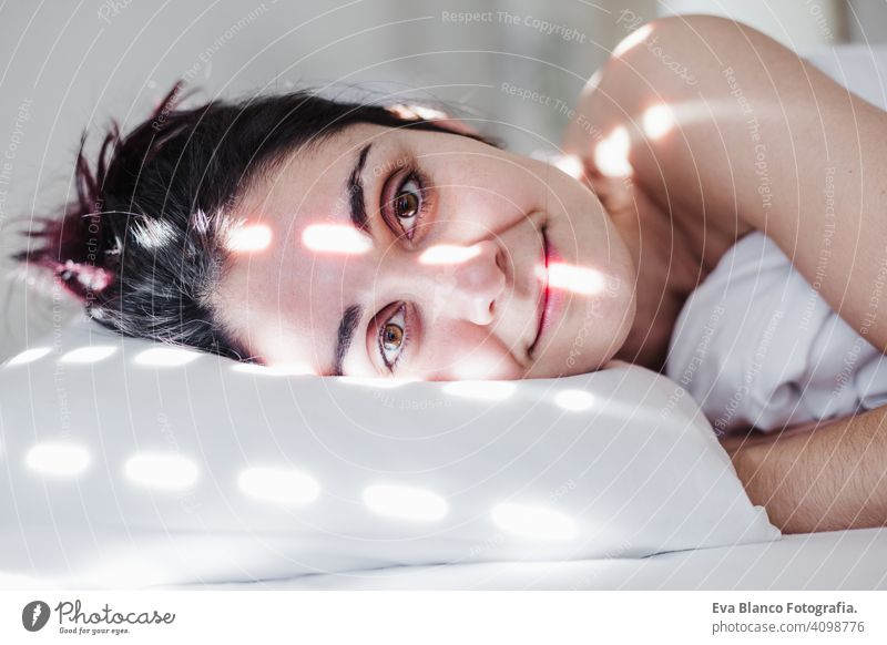 portrait of attractive young caucasian woman relaxing in bed during morning time. Lady enjoys fresh soft bedding linen and mattress in bedroom sleeping nap