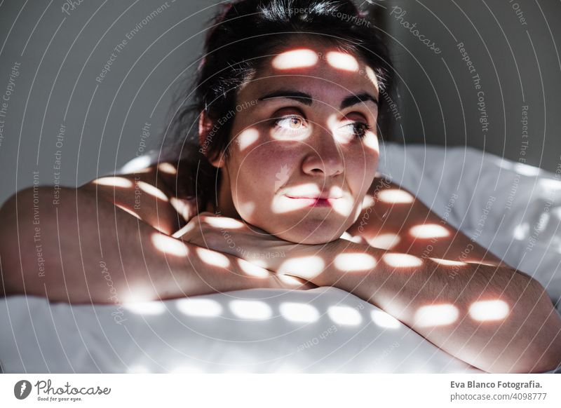 portrait of attractive young caucasian woman relaxing in bed during morning time. Lady enjoys fresh soft bedding linen and mattress in bedroom. Blind shadows on face