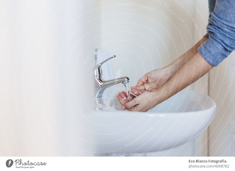 Closeup of caucasian woman washing hands in bathroom to prevent Covid-19 viral infection. Recommended washing with soap and running water during coronavirus pandemic