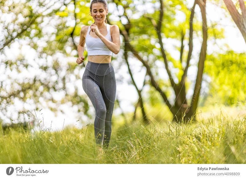 Fit young woman exercising in nature natural girl people female recreation healthy wellbeing lifestyle active vitality outdoors adult outside attractive