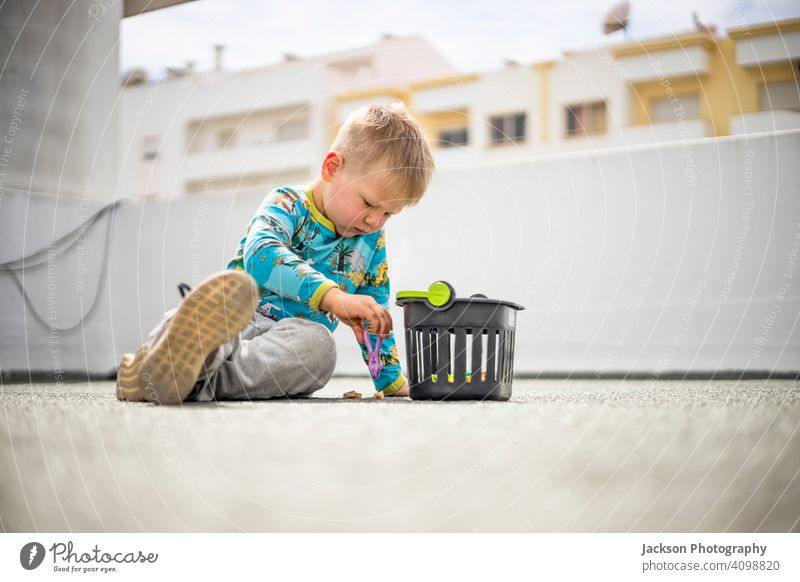 Small boy playing with colorful clothes pegs on the rooftop of his apartment building lockdown game fun toy small roof top covid covid 19 pandemic basket