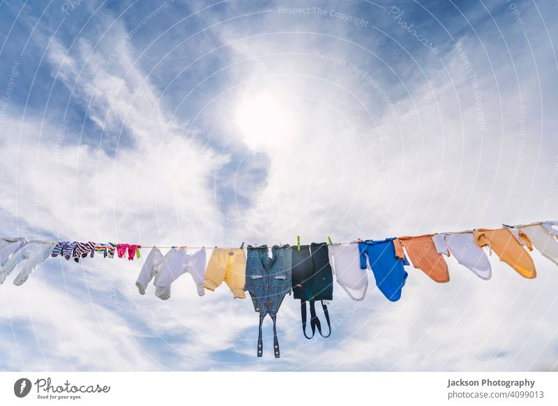 A lot of small baby clothes hanging  against blue sky dry laundry pin architecture body grow boy building care child city clean clothesline clothing cord cotton