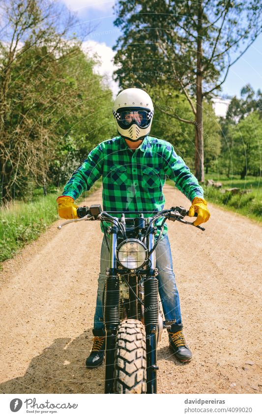 Man with helmet riding custom motorbike man biker defiant vintage retro rider vehicle transport motorcycle posing young adult one people person real