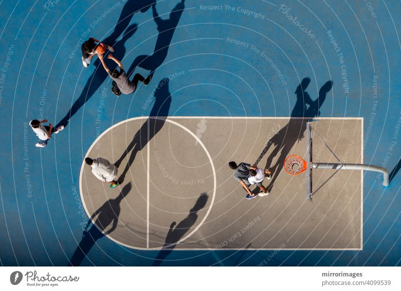 young man playing basketball at dusk or morning light with long shadows high angle bird's eye view netted hoop court b-ball high angle view hoops in city courts