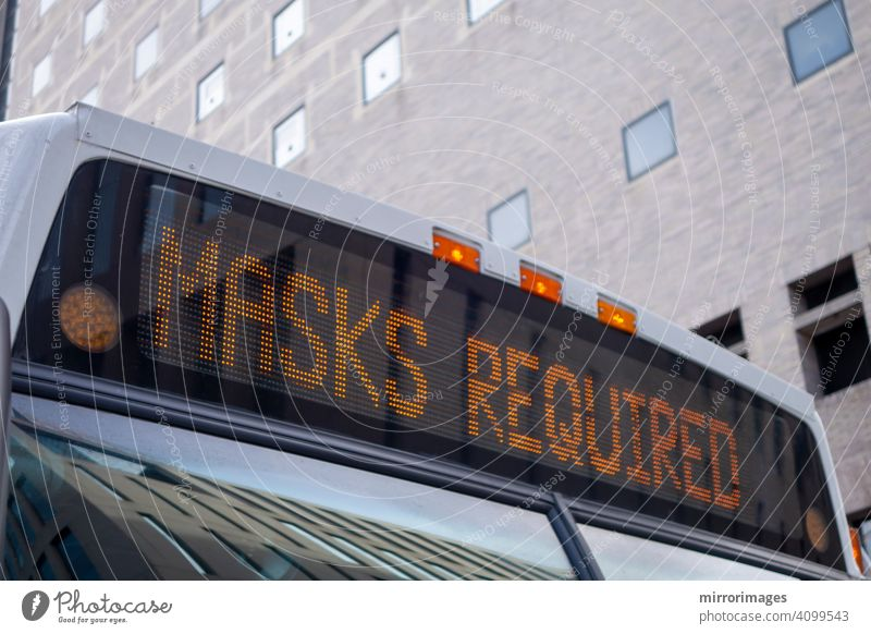 the front top of a city bus with a lighted sign reading Masks Required corona virus passenger bus transportation corvid 19 pandemic new york avenue vehicle