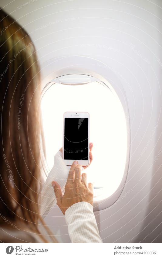 Woman turning on smartphone nearby window in plane flight using browsing woman surfing mobile passenger trip device gadget airplane female vacation aircraft