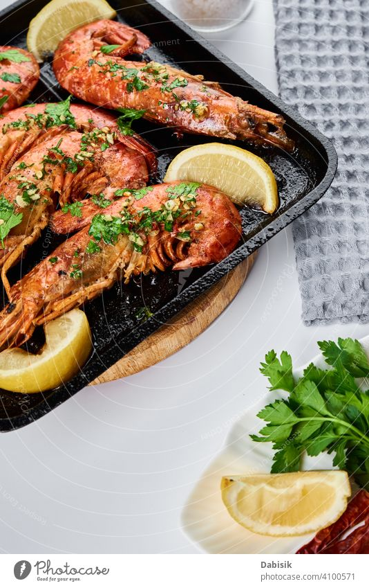 Grilled large queen shrimps with lemon and spices on the grill pan prawns seafood red background dark black dish tiger cooked crayfish eating gourmet healthy
