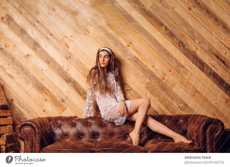 Young woman in white dress sitting on couch young interior female hipster brown legs fashion portrait person wooden room people girl sofa caucasian model hair