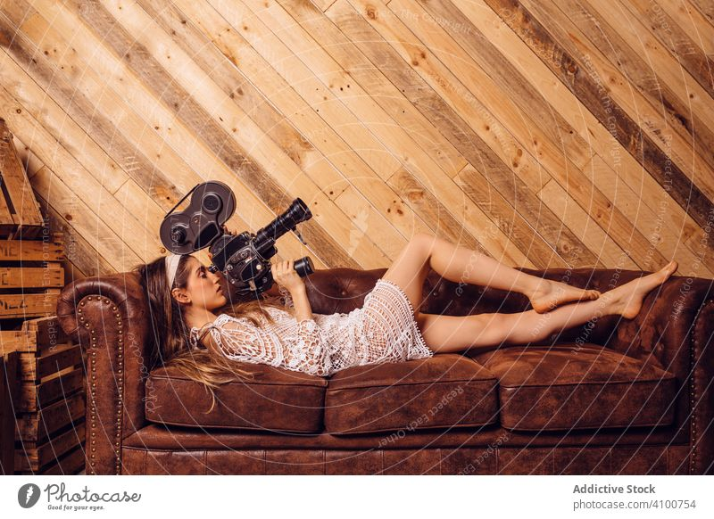Young woman recording video with a vintage camera cinema videography videographer wood couch antique device camerawoman concept brown hipster filming funny