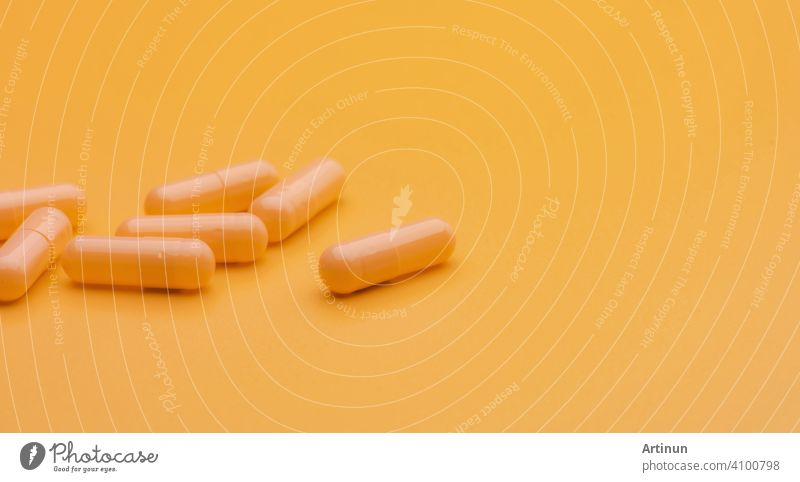 Yellow capsule pills on yellow background with copy space. Pharmacy and health insurance concept. Prescription drugs. Pharmaceutical industry. Vitamins and supplements. Marketing for pharmacy company.