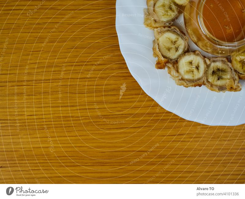 Delicious Fried slices of the ripe plantain and a glass of honey making a beehive on a round wooden plate. Top View plantains dessert banana fritter eat