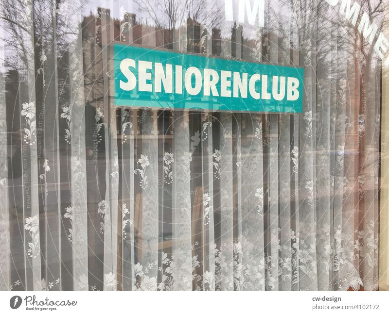 Sign from ˋSeniors Clubˋwith curtain in shop window Senior Citizens Club Curtain Shop window Store premises window display window dressing Shop window facade