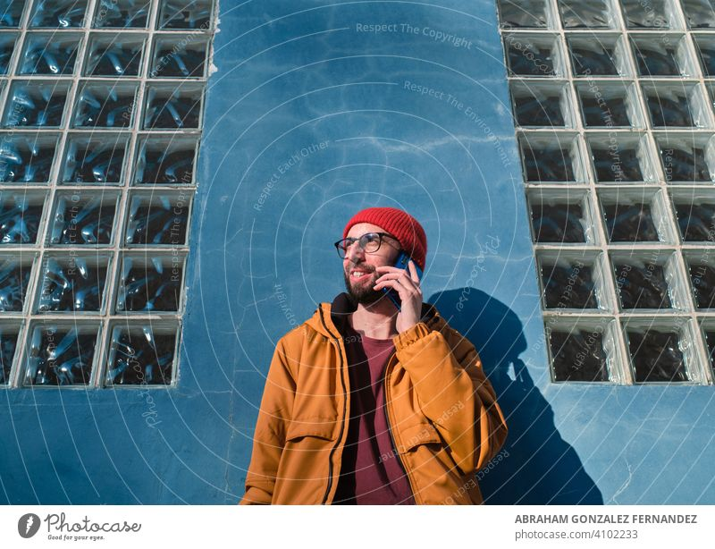 young man talking on his smartphone leaning against a blue wall lifestyle people communication smiling technology using horizontal call telephone hipster