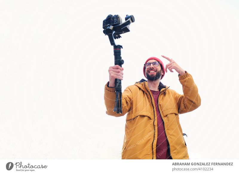 videographer filming himself with a dslr camera on a motorized gimbal with a white background videography movement production man shoot stable anti blur