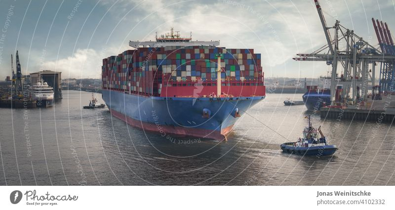 Container terminal in the port of Hamburg with large container ship and tugs ships marine pier steel commercial bulk commerce heavy global europe blue economy