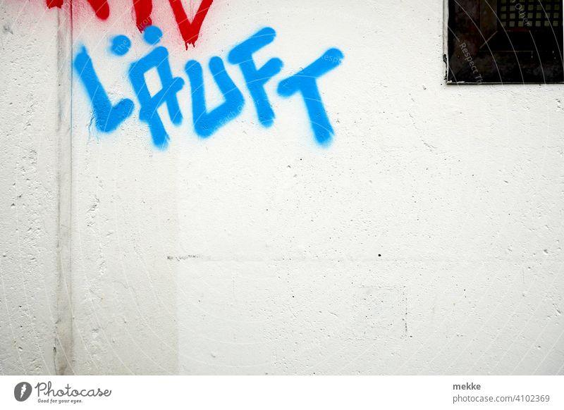 Runs graffiti on white house wall writing Blue mural painting Text running embassy Colour German sprayed Grafitto Wall (barrier) urban Town slogan Street