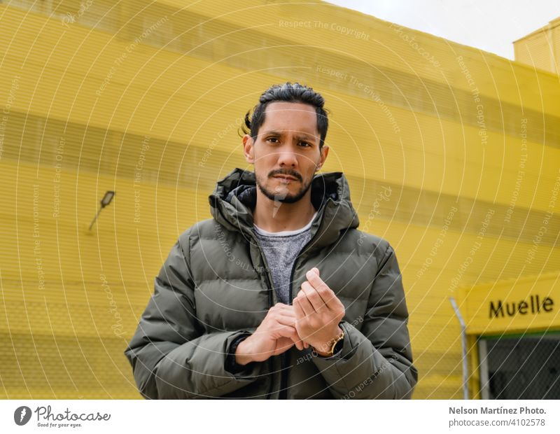 portrait of a hispanic man in a yellow background local business sunlight day one person hispanic ethnicity confident casual clothing young adult work