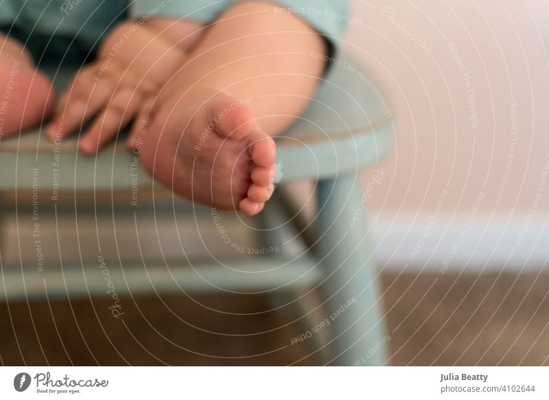 Close up of sweet chubby baby feet and hands; baby seated in turquoise wood chair independent child foot toddler sit toes care human kid childhood little family