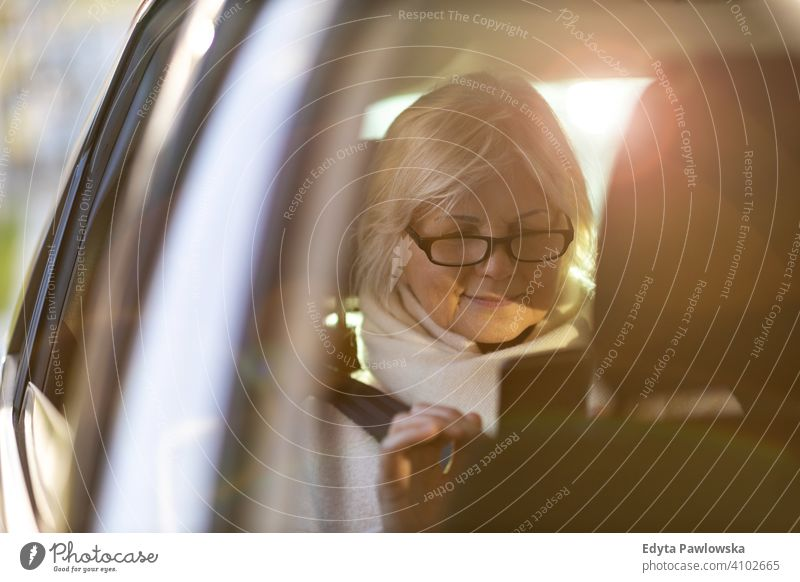 Senior woman with smartphone on the back seat of a car people one person senior mature pensioners retiree retired retirement old elderly gray hair caucasian