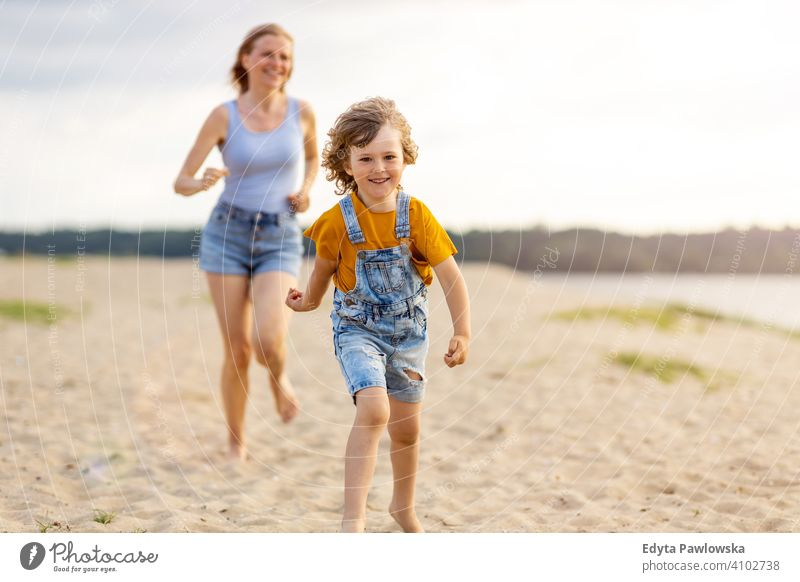 Mother and a child enjoying a day at the beach sea lake holidays vacation nature summer family parents son boy kids children together togetherness love people