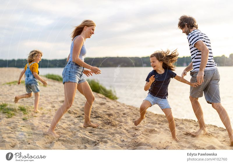 Young family having fun outdoors at the beach Beach Ocean Lake holidays vacation Nature Summer Family Parents Son Boy (child) children Together
