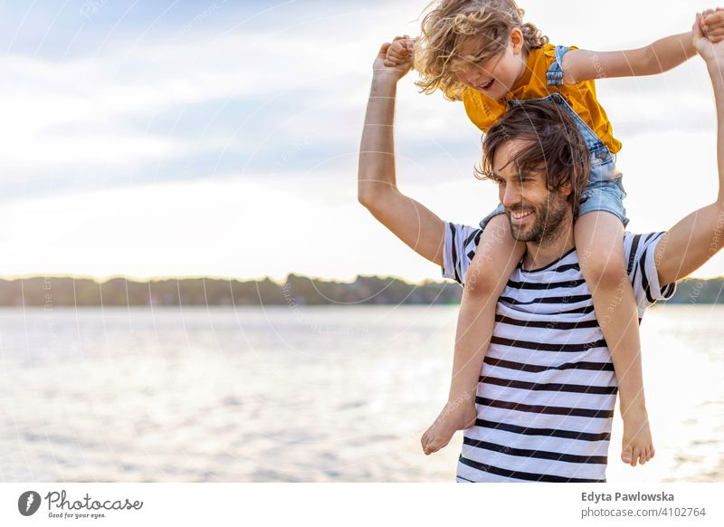 Father with a child spending the day at the beach sea lake holidays vacation nature summer family parents son boy kids children together togetherness love