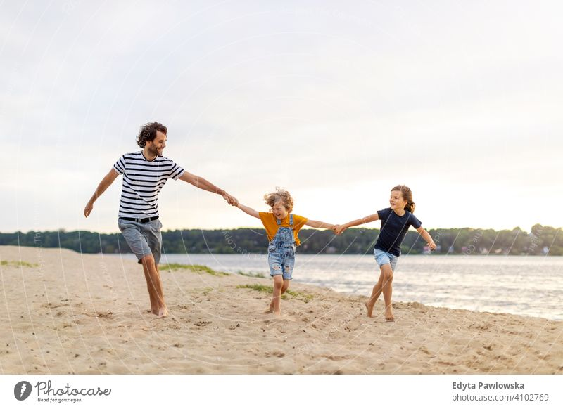 Father with two children enjoying a day at the beach sea lake holidays vacation nature summer family parents son boy kids together togetherness love people