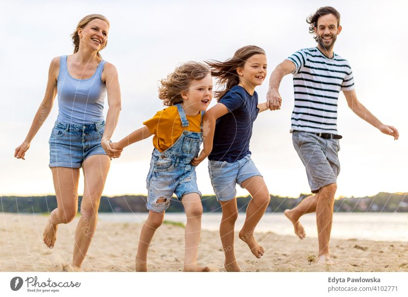 Young family having fun outdoors at the beach sea lake holidays vacation nature summer parents son boy kids children together togetherness love people happy
