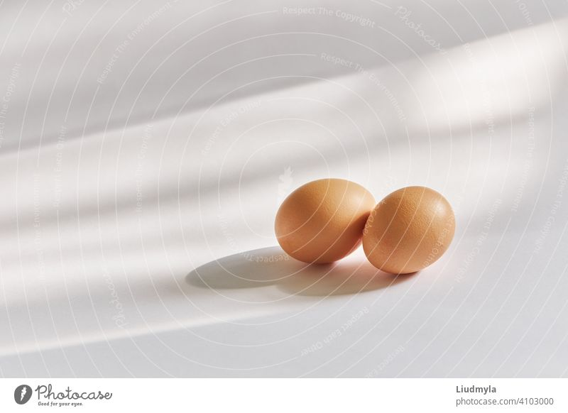 Two brown eggs on a white background in natural sun light shadows feathers two product prepared celebration cook lunch space greeting fresh fragile group