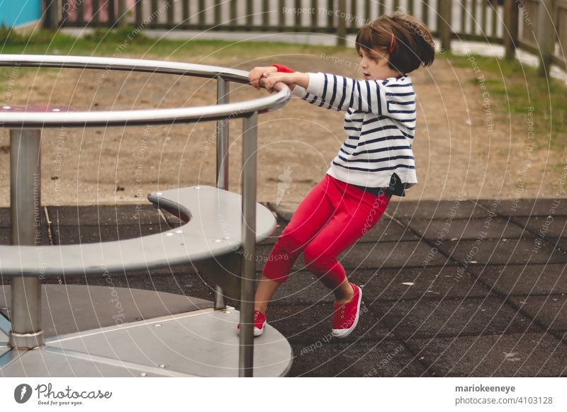 Side view of a little girl propelling a spinning carousel in a playground active activity agility amusement amusing caucasian challenge child child play