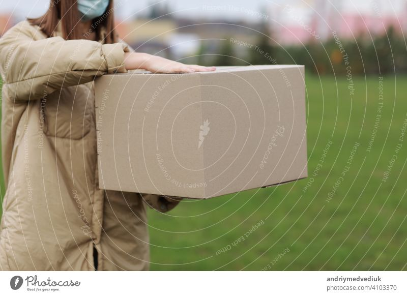 Delivery girl in face medical mask hold empty cardboard box outdoors on a residential complex background. Service coronavirus. Online shopping. mock up.