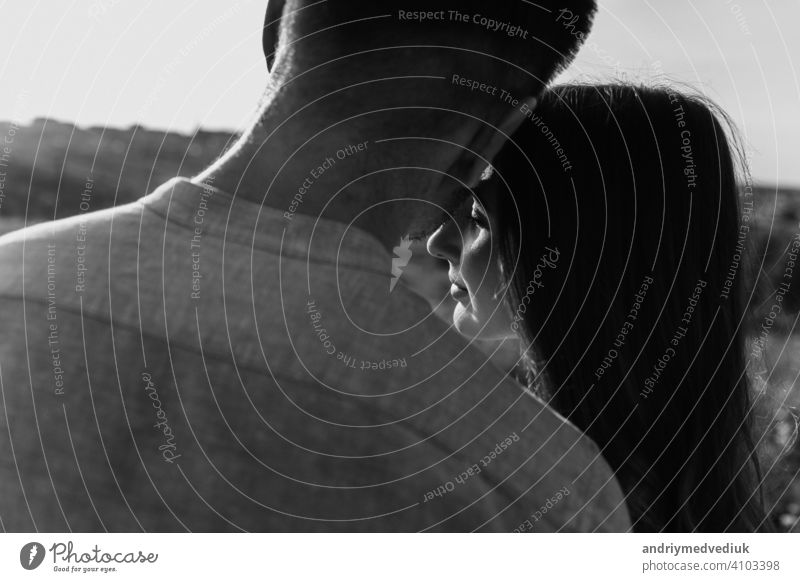 black and white photo of young loving couple hugging outside. concept of happiness and love. close up photo. love story portrait season together people fun body