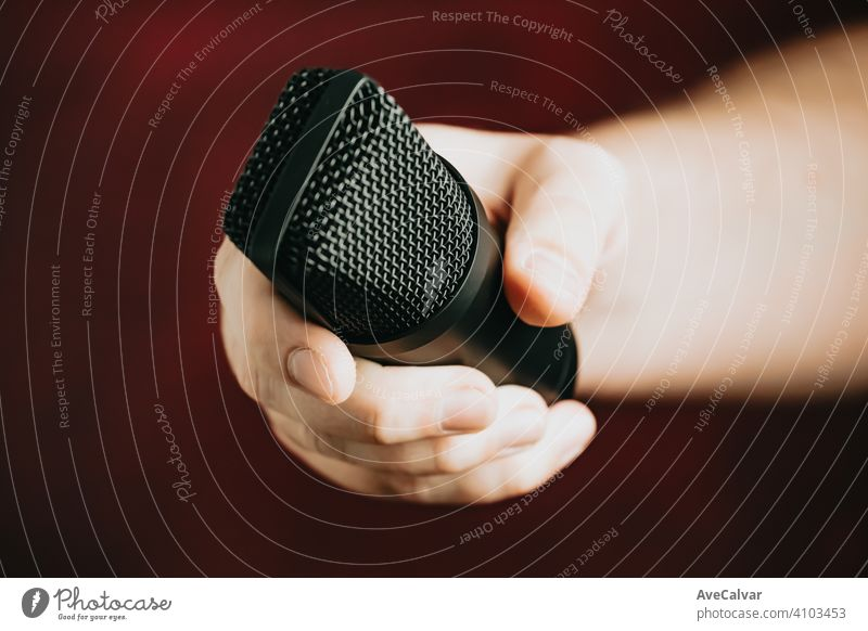 A hand grabbing a microphone over a red background record audio technology music professional sound radio recording studio apartment display dof dynamic