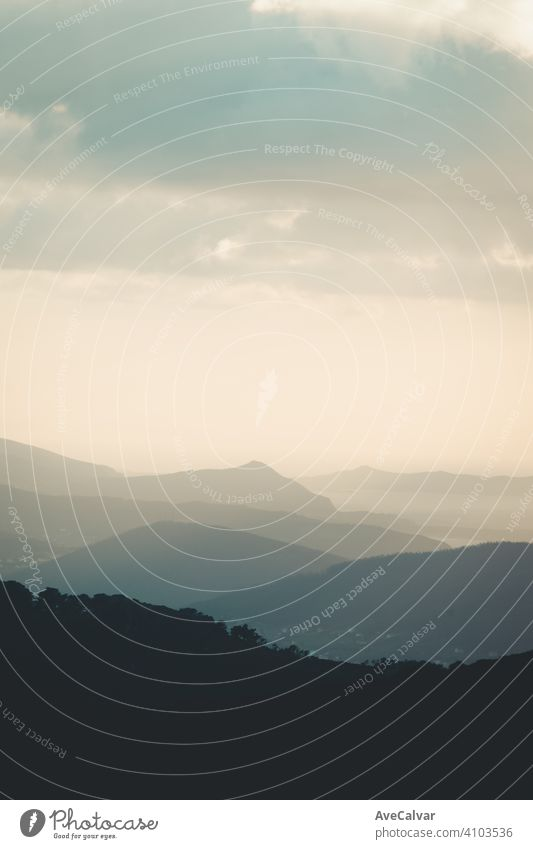 A mountain near the ocean liberty concept with copy space and dark shadows and contrasts inspiration sunrise range exploration flare glowing lens magical ray