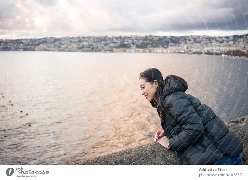 Woman on vacation in warm wear delighting in sunset on seashore woman cloud sky smile female enjoy laugh travel tourism relax water beautiful beach holiday