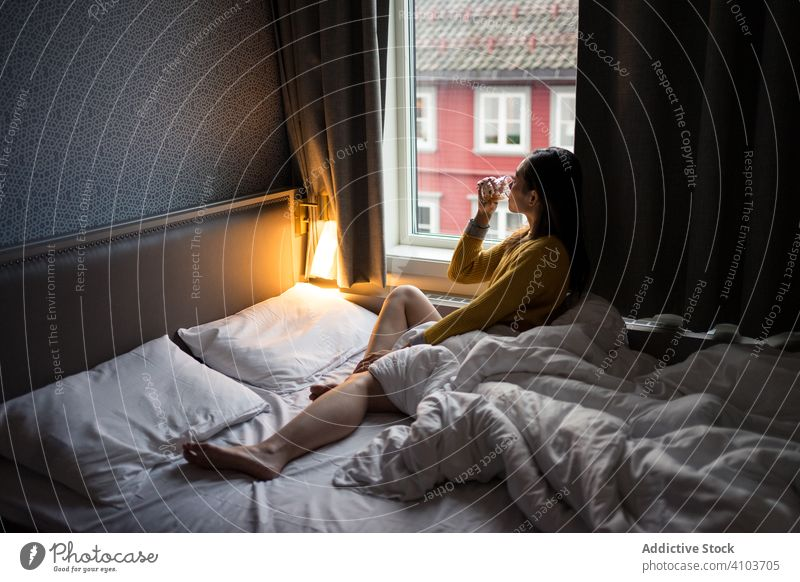 Anonymous female on vacation delighting in view in window while drinking tea in morning woman bed sitting looking sweater coffee cup home relax breakfast