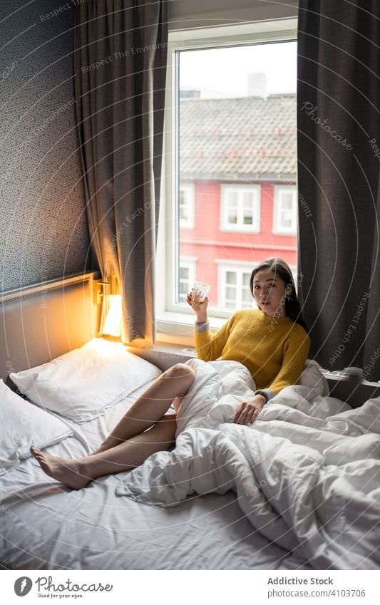 Female drinking tea in morning woman bed sitting looking window view sweater coffee cup home female relax breakfast beverage mug hot lifestyle casual cold