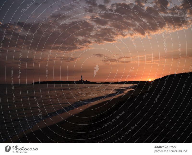 Beautiful sunset over sea with cloudy sky clouds water ray evening dark coast beach shore calm shoreline tranquil ocean light summer coastline horizon travel
