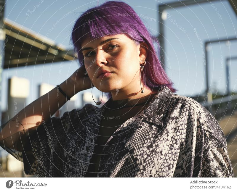 Woman with purple hair looking at camera woman stylish urban hairstyle construction shiny structure district confident fashion young model street human female