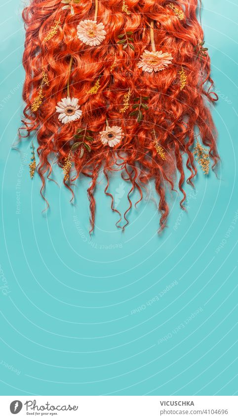 Red ginger curved hair background with flowers on turquoise blue background. Beauty and hair styling concept. red beauty green leaves cosmetic product bottle